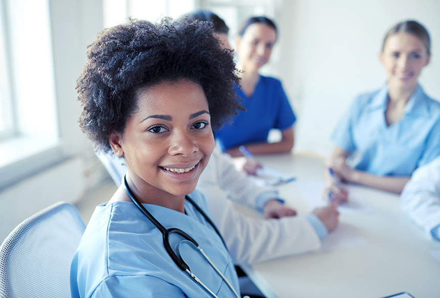 health care, profession, people and medicine concept - happy african american female doctor or nurse over group of medics meeting at hospital
